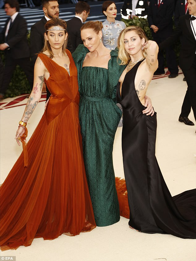 Trio: The 20-year-old model arrived alongside designer Stella McCartney and singer Miley Cyrus dressed in a longburnt sienna frock and a tiara