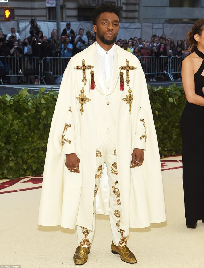 Chadwick Boseman donned a custom Versace - complete with elaborate embroidery - with a full-length cape and Christian crosses