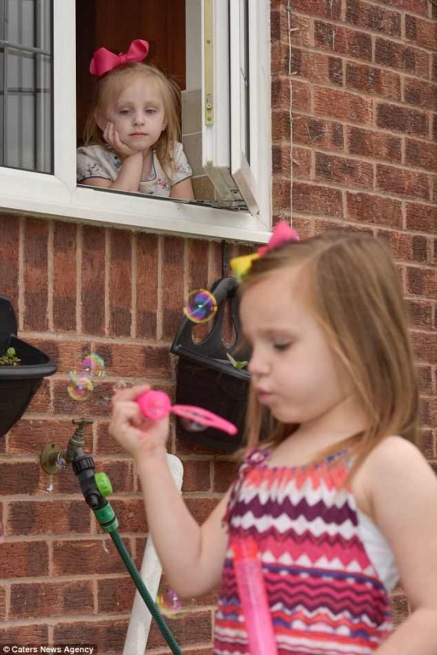 Ms Pickles is now searching for answers from doctors as to why her Carys, who has two older sisters, is a 'walking allergy', and how to stop the pain (Carys pictured inside while her sister Amelia blows bubbles in the garden)