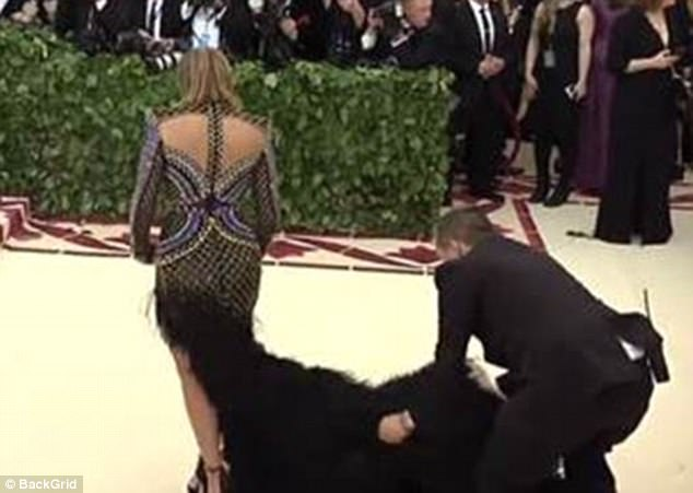 An assistant was seen helping Jennifer Lopez re-arrange her train on the red carpet