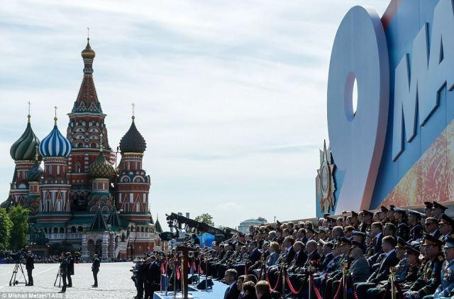 記念碑に招待されたゲストは、バックグラウンドで聖バジル大聖堂のある赤い広場の横に座っています