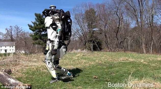 In one video, Atlas, a humanoid robot, can be seen jogging around a grassy field, before leaping over a log that's obstructing its path. This image shows it preparing for the leap
