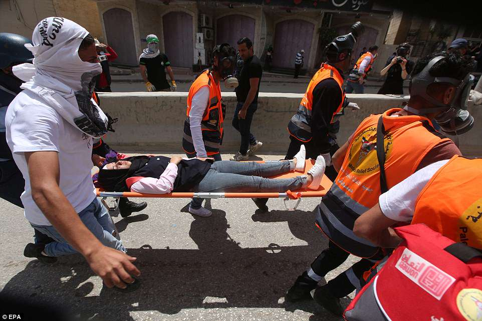 A wounded female Palestinian demonstrator is evacuated on a stretcher by emergency workers at Qalandya checkpoint near the West Bank city of Ramallah