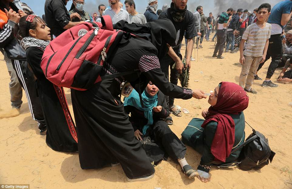 A woman appears to be giving protesters medical assistance as she tends to them while they sit on the ground during clashes along the border with Israel