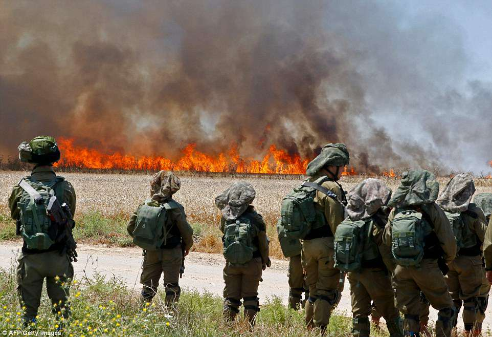 Israeli soldiers walk amidst smoke from a fire in a wheat field near the Kibbutz of Nahal Oz, along the border with the Gaza Strip today