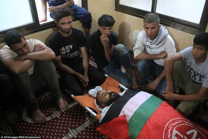 Grieving relatives are gearing up for a day of funerals after what was the deadliest single day in the Israeli -Palestinian conflict since a 2014 war between the Jewish state and Gaza's Islamist rulers Hamas. Relatives of one of the dead sit around his body ahead of a day of funerals in the enclave