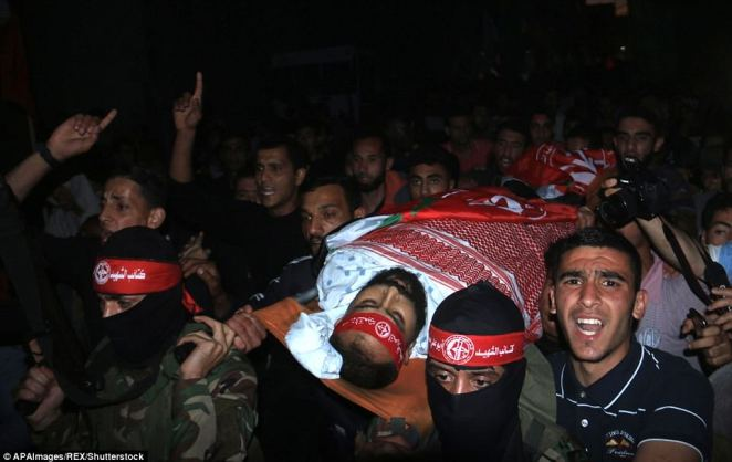 Mourners are pictured carrying the body of Palestinian Ahmed al-Adini, 30, who was killed by Israeli troops during clashes on the Gaza border yesterday