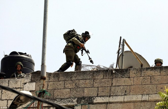 On a tense day in the region, Israeli soldiers could be seen taking position during clashes with Palestinian protesters in the West Bank city of Hebron