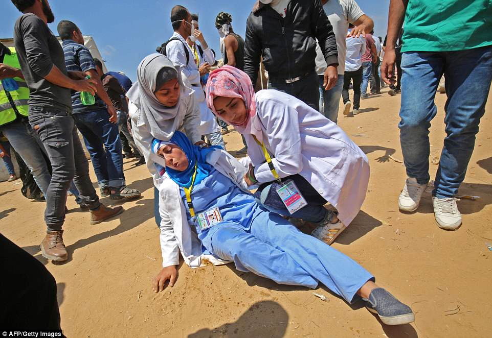 Palestinian female medics tend to an injured colleague during clashes near the border with Israel, east of Khan Yunis in the southern Gaza Strip, on Thursday