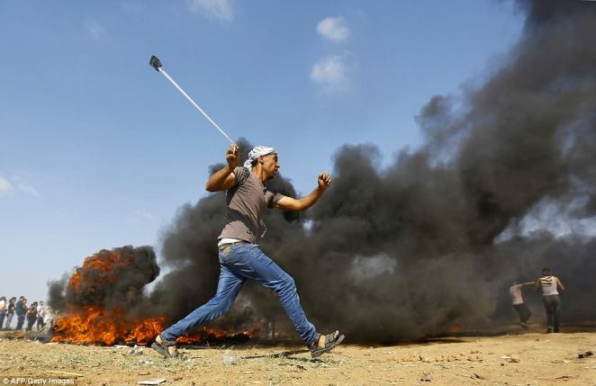A Palestinian man hurls a stone during clashes with Israeli forces on May 15, 2018 near the border fence with Israel today as the region suffers its most deadly protests in years