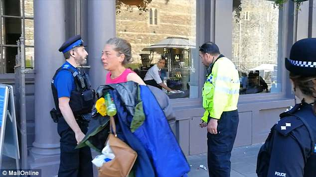 The officers ask two homeless men, who had pitched up this afternoon outside a Barclay's Bank opposite Windsor Castle, to pack up their items in see-through bags