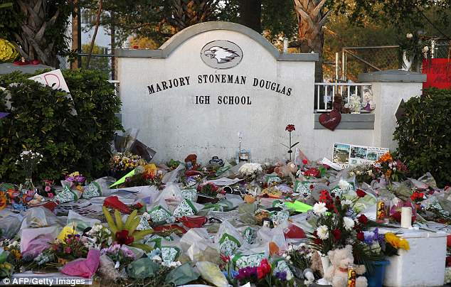 Flowers, candles and mementos sit outside one of the makeshift memorials at Marjory Stoneman Douglas High School in Parkland, Florida on February 27, two weeks after 17 people were killed in a shooting