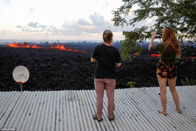 Jolon Clinton, 15, and her sister, Halcy, 17, take photos of a fissure near their home on the outskirts of Pahoa during ongoing eruptions of the Kilauea Volcano
