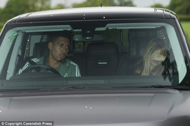 Chris Smalling's wife, Sam Cooke, covered her face from photographers as the pair arrived