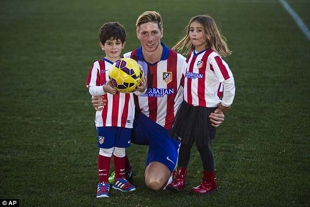 Torres and his children, Leo and Nora, pose in Atletico shirts after he rejoined the club