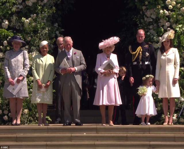 Lady Jane Fellowes (far left) and Meghan's mother Doria Ragland (next to her, in green) stand next to Prince Charles, Camilla, George, William, Charlotte and Kate on the steps of St George's Chapel today after the wedding