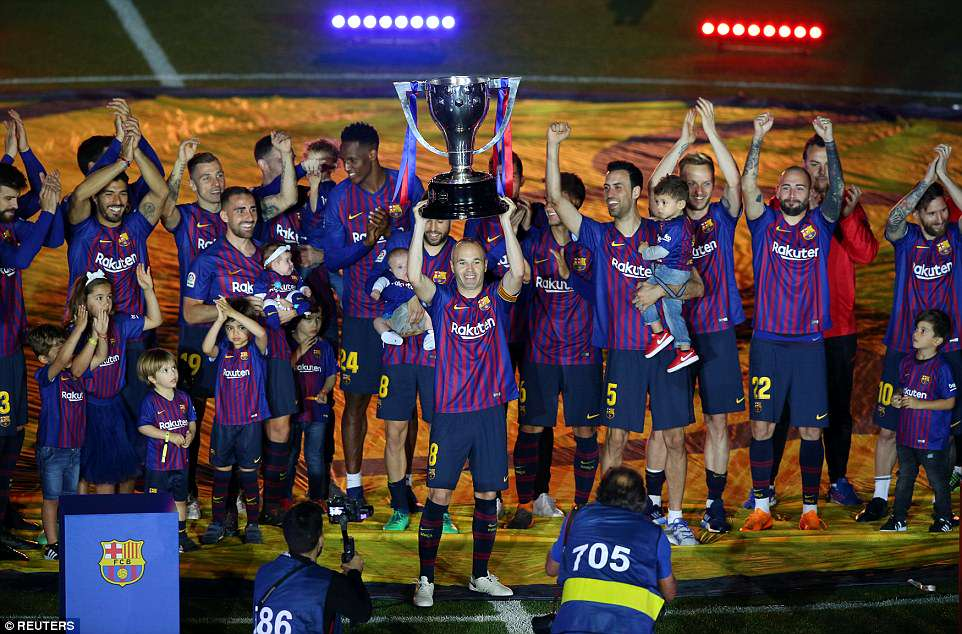 Iniesta paraded the club's latest La Liga title trophy around the stadium as the Catalan players celebrated with close family