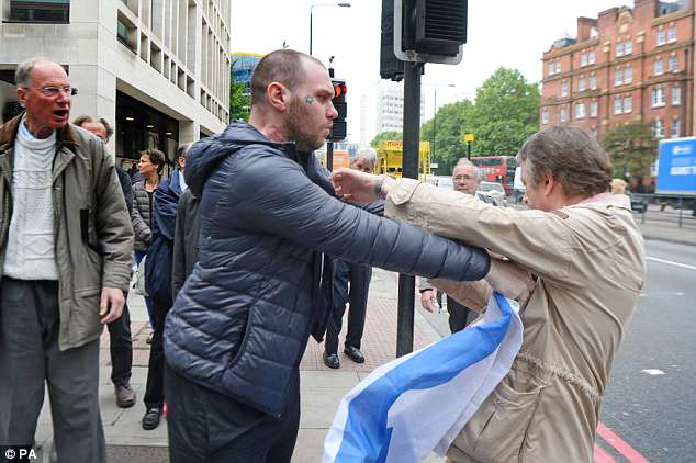 A man with an Israeli flag was seen jostling with another man outside the court building