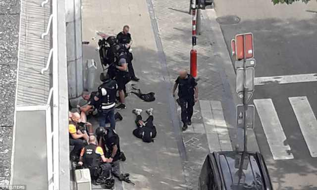 Down: Police special forces are seen next to the body of what is believed to be the attacker, outside the high school