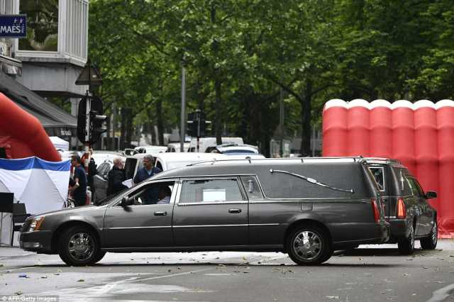 Hearses are parked near a police tent at the scene where a gunman shot dead two police officers and a bystander on the Boulevard d'Avroy in Liege
