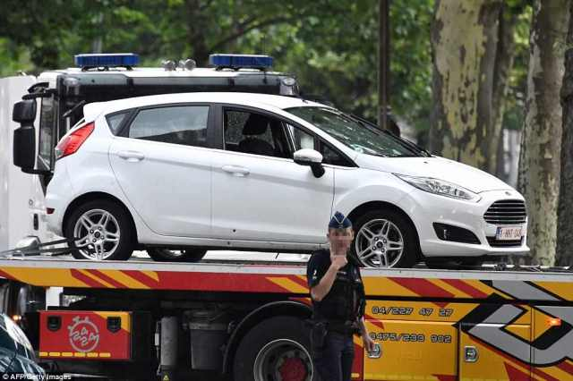 A white car is towed away away from the scene of the shooting today in Belgium as a police officer stands at the scene in Liege