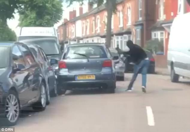 Another man then appears to launch a hammer (pictured) at the car windscreen before fleeing with his accomplice