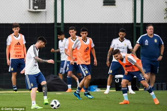 Messi (L) takes on his some of his Argentinian team-mates during a training session