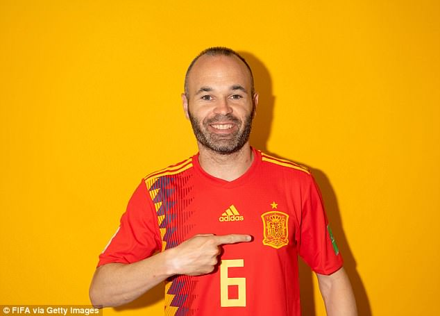 Barcelona legend Andres Iniesta, wearing No 6, points to the Spain crest below the golden star