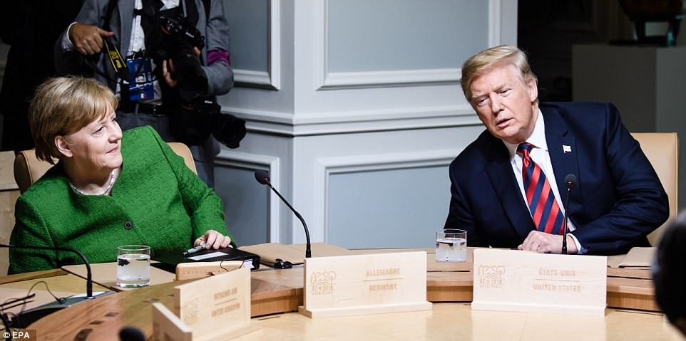 Working together: Trump and Merkle had a rare moment of synchronicity as they both reached under the table