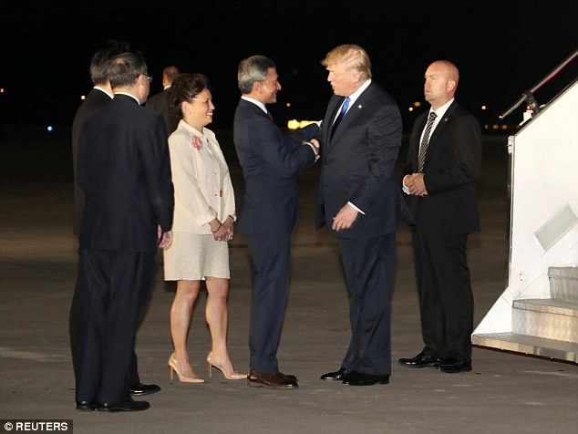 President Donald Trump is met by Singapore's Foreign Minister Vivian Balakrishnan and other officials after arriving for his summit with North Korea