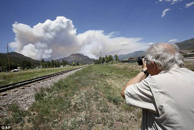 Paul Boyer of Durango, Colorado, levels his camera for a shot of the plume as it rises from the wildfire near Hermosa