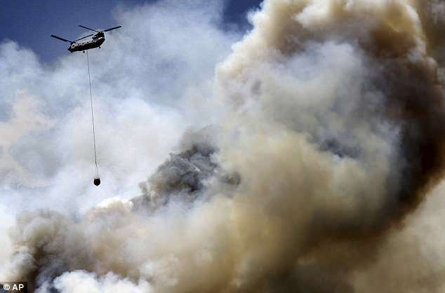 A helicopter is seen flying over Hermosa Cliffs near Hermosa, Colorado as authorities try to get wildfires under control on Saturday