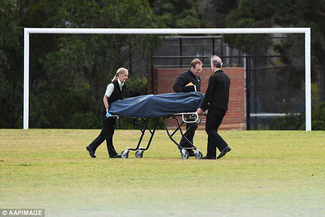 Pictured is the body being removed from the park in the inner Melbourne suburb of Carlton North