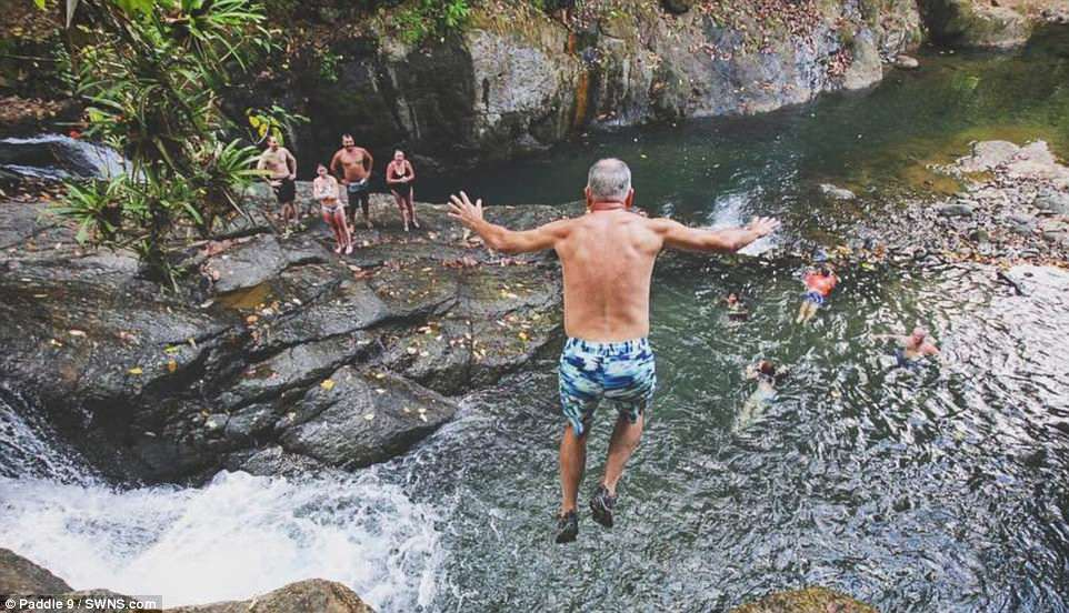 An older gentleman enjoys the drop from 30ft as fellow thrill-seeking tourists look on. The guides They have so far been taking groups of people around the Nauyaca Waterfall
