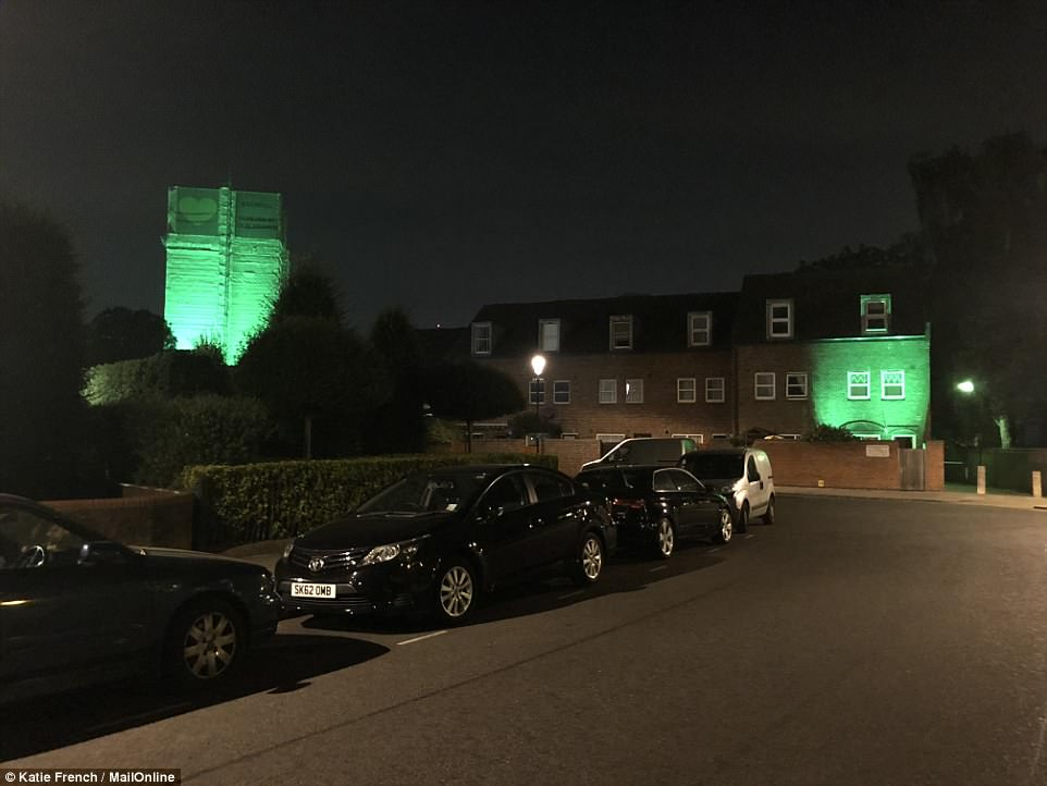 A house close to Grenfell Tower is lit up in bright green light tonight as a community comes together to mark the one-year anniversary of the tragedy