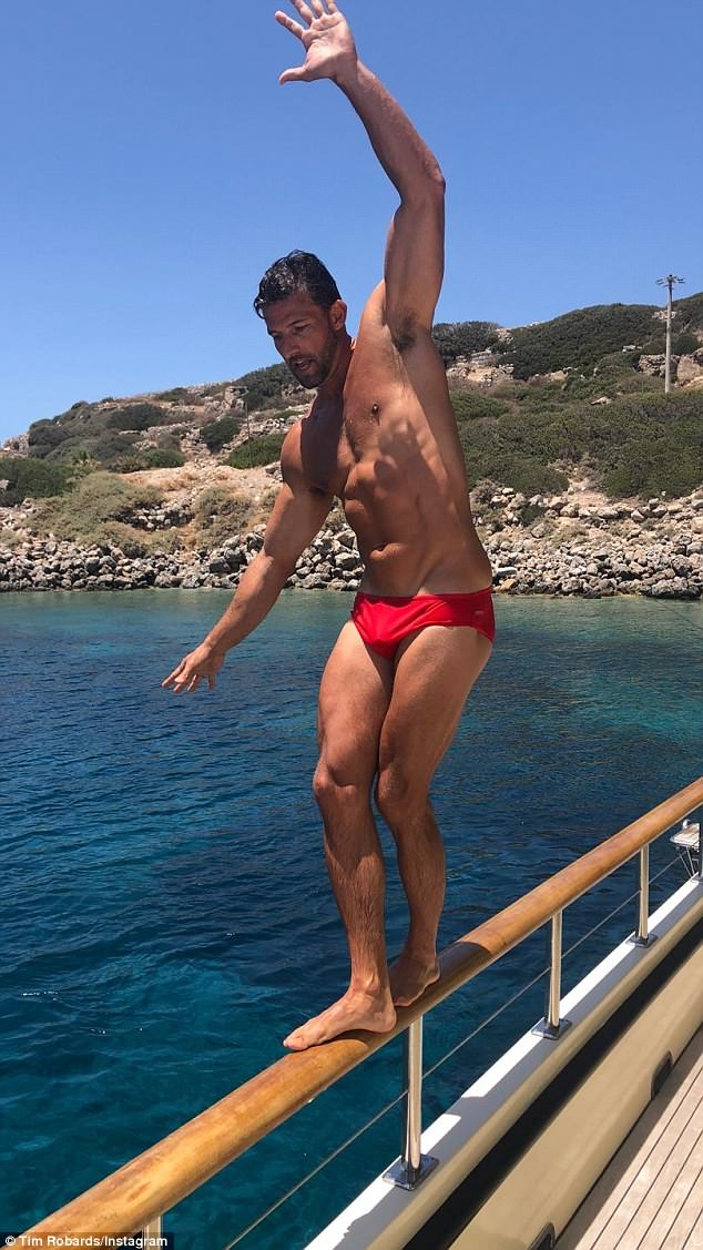 Red alert: In footage from their wild boat party, Tim is shown balancing on the railing of the vessel in a pair of skimpy red Speedos