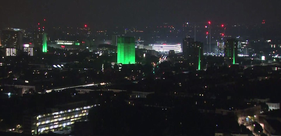 Poignant: Grenfell Tower (pictured centre) and neighbouring blocks illuminated green to mark one year since the disaster