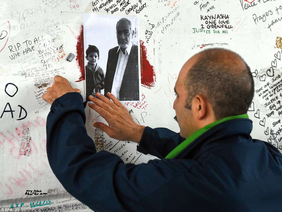 Hamid Ali Jafari places a picture of his father, Ali Yawar Jafari on a wall of messages under the Westway Flyover in teh shadow of Grenfell