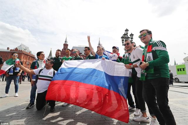 Locals wave the Russian flag in the centre of Moscow as they pose with visiting Mexican supporters ahead of the tournament