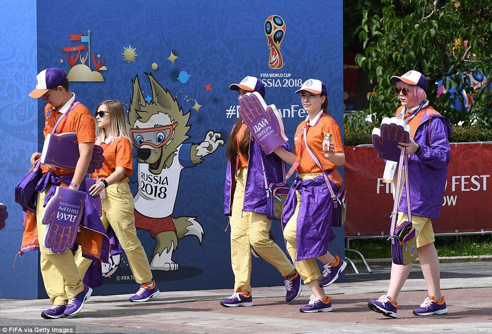 Volunteers in colourful orange and purple costumes arrive at the Fan Festival in Moscow as the tournament gets underway