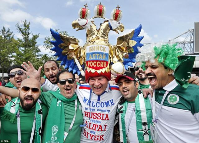 A Russian supporter wearing elaborate headgear posed with Saudi Arabian fans in Moscow ahead of the World Cup opener