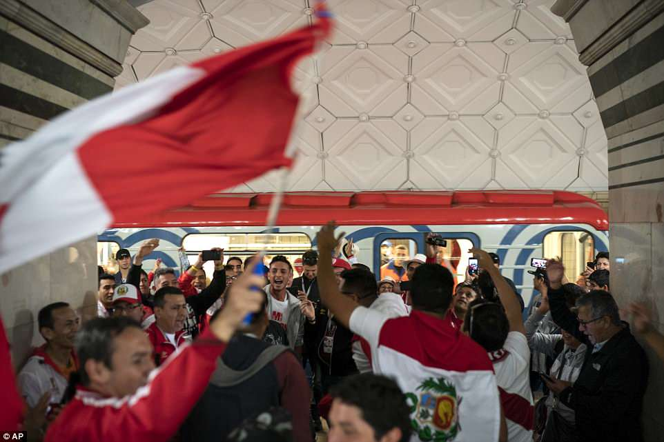 Peru fans cheer and wave their red and white national flag as they exit the Metro close to the Luzhniki Stadium on Thursday