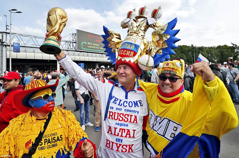 This Russian fans made an effort to welcome visitors from all nations, posing here with a couple of colourful Colombians