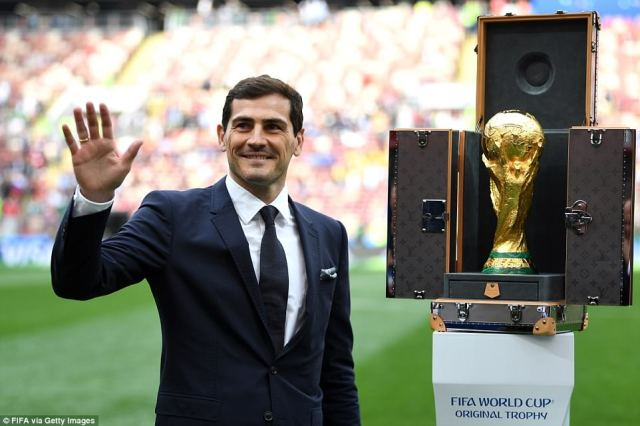 Casillas raises his hand to acknowledge the crowd after placing the trophy on a plinth, denoting it is up for grabs once more
