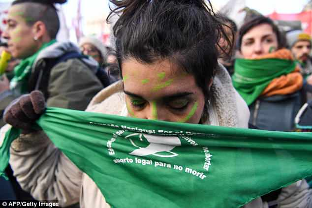 An abortion rights activist kisses her pro-choice scarf as she hears the news that the bill has passed