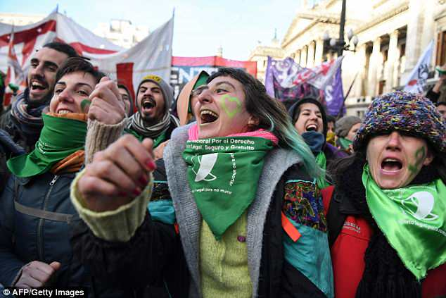 The debate has divided Argentine society, which is still heavily influenced by the Catholic Church. Pictured: Campaigners cheer as they hear the news that the bill has passed today