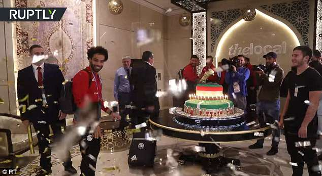 Salah (second left) smiles at the celebrations as he is presented with the gigantic cake