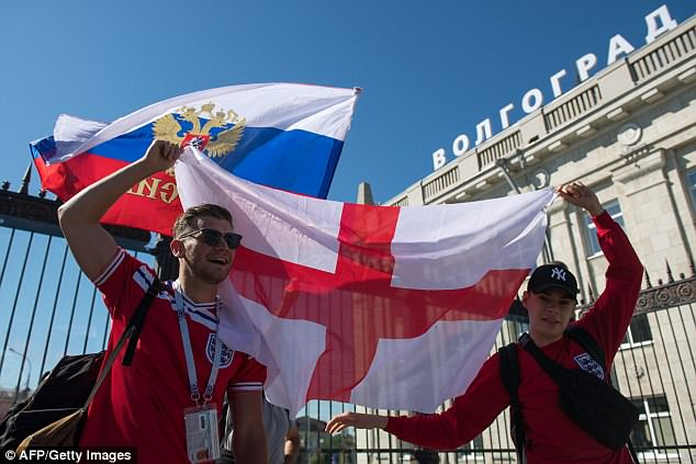 England football fans wave flags as they arrive at the Volgograd railway station in Volgograd