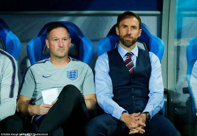 England manager Gareth Southgate and his assistant Manager Steve Holland take their seats in the dugout ahead of kick off