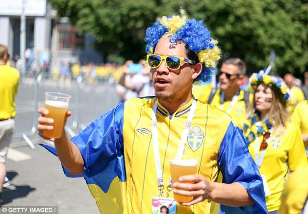 A Sweden supporter carries two glasses of beer - fans are in danger of drinking Moscow dry
